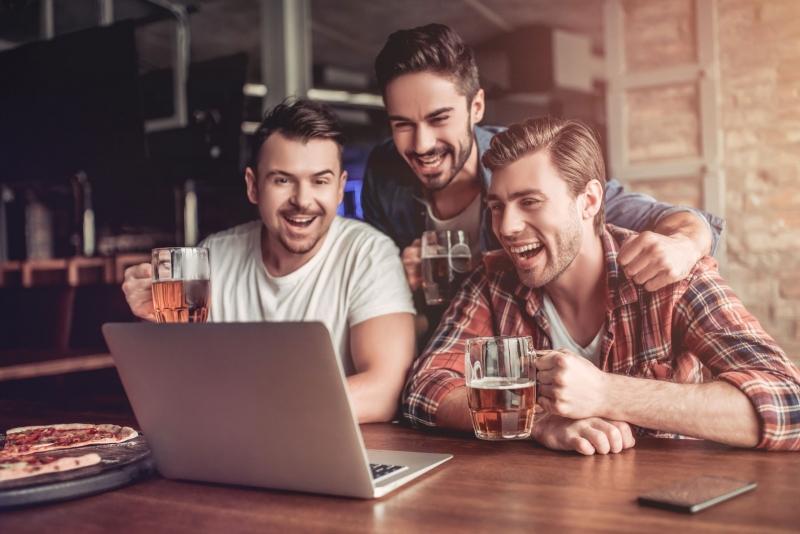 Muži s pivem se dívají na notebook