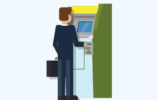 muž stojí u bankomatu