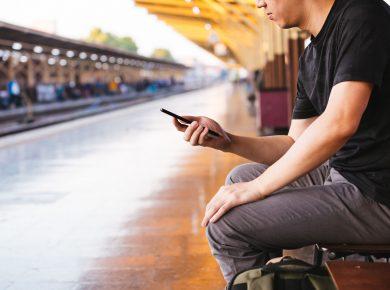 Muž s telefonem na nádraží